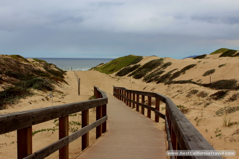 Oso Flaco Lake, California - Wooden path leads to the ocean beach through sand dunes.